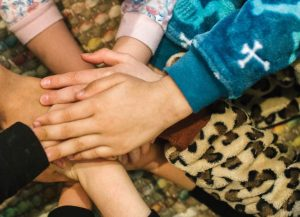 Children's hands covering each other's