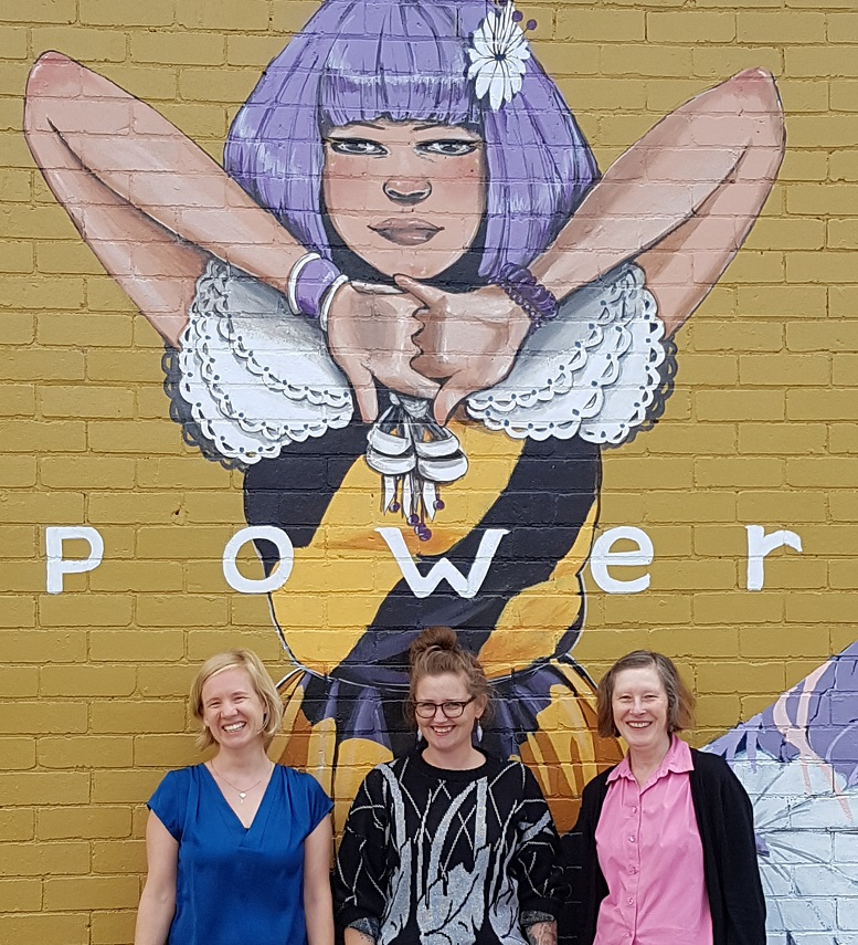 Photo of three women below a mural of a woman with word POWER written across her chest
